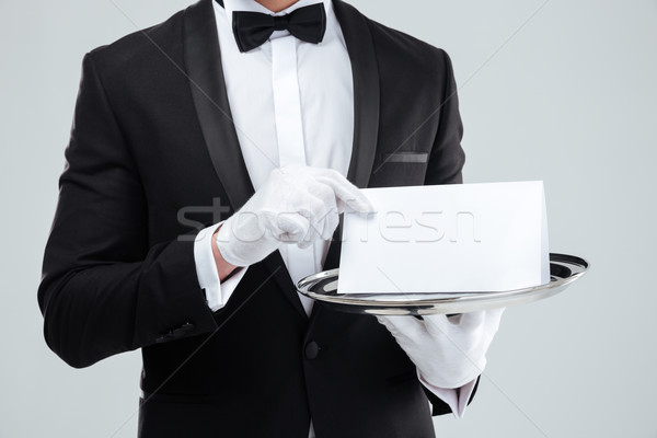 Butler in tuxedo and gloves holding blank card on tray Stock photo © deandrobot
