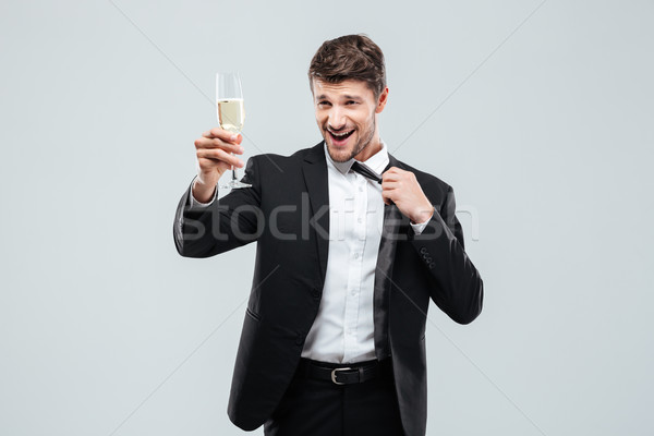 Happy businessman with glass of chamagne standing and making cheers Stock photo © deandrobot