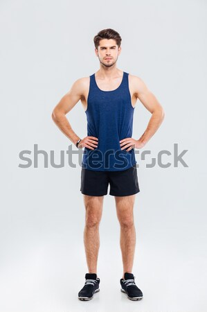 Full length portrait of sportsman standing with hands on hips Stock photo © deandrobot