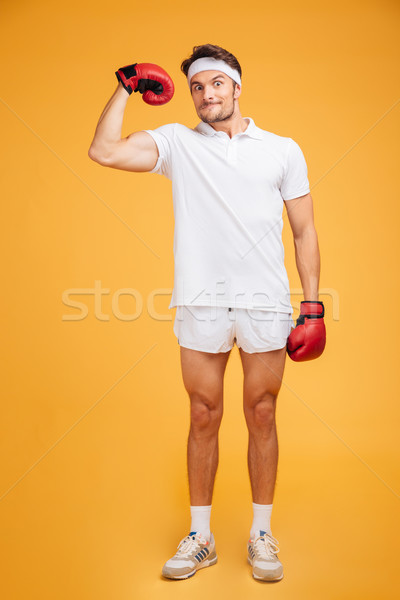 Funny man boxer in red gloves standing and showing biceps Stock photo © deandrobot
