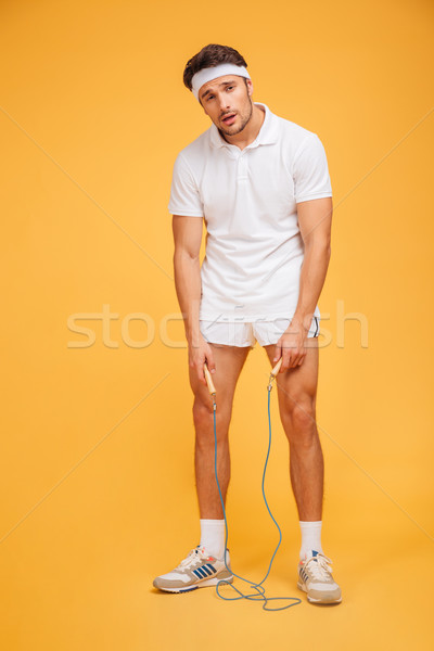 Full length portrait of a tired sportsman holding skipping rope Stock photo © deandrobot