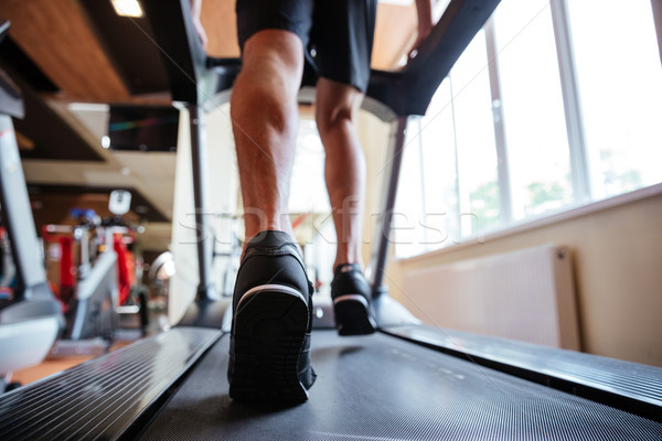 Back view of young sportsman running on treadmill in gym Stock photo © deandrobot