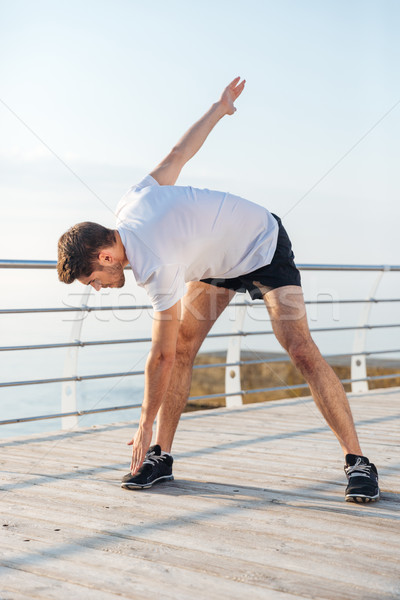 Serious young man athlete warming up and doing exercises Stock photo © deandrobot
