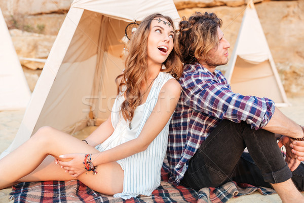 Surprised couple looking to the side near teepee on beach Stock photo © deandrobot