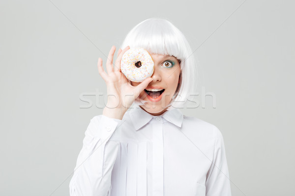 Cheerful woman in blonde wig covered her eye with donut Stock photo © deandrobot