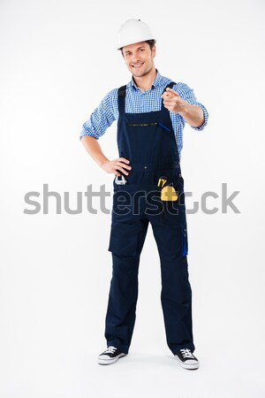 Smiling young man foreman in hard hat pointing on you Stock photo © deandrobot