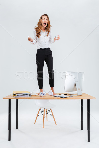 Angry mad young businesswoman standing on table and screaming Stock photo © deandrobot