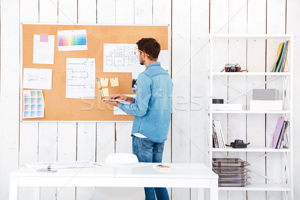 Back view of a man looking at the task board Stock photo © deandrobot