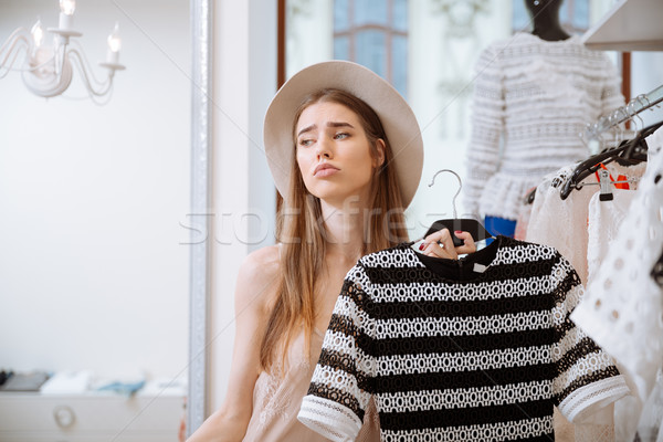 Sad pretty young woman in hat doing shopping Stock photo © deandrobot