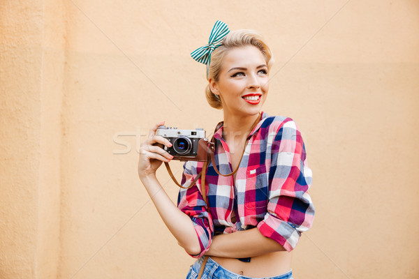 Beautiful cheerful pinup girl in yellow dress using vintage camera Stock photo © deandrobot