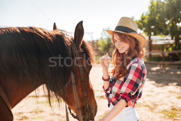 Cute lovely cowgirl taking care of her horse on ranch Stock photo © deandrobot