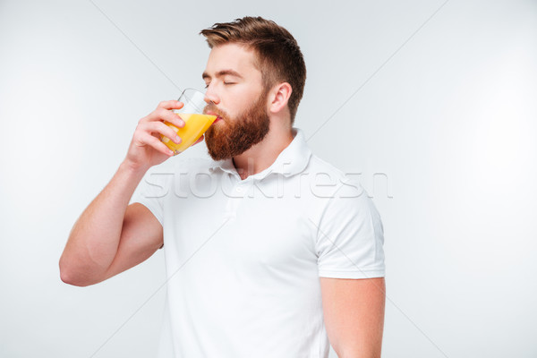 Genç yakışıklı sakallı adam içme portakal suyu Stok fotoğraf © deandrobot