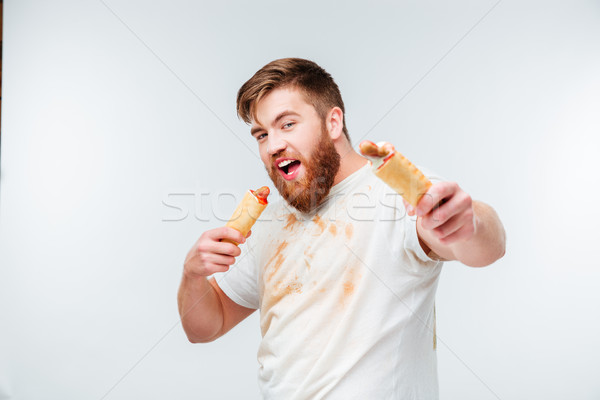Hungry man in dirty shirt going to eat two hotdogs Stock photo © deandrobot