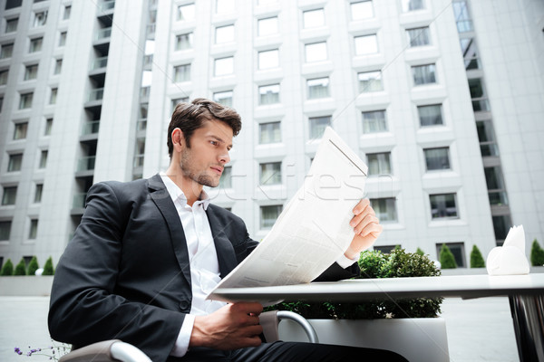 Businessman reading newspaper in outdoor cafe Stock photo © deandrobot