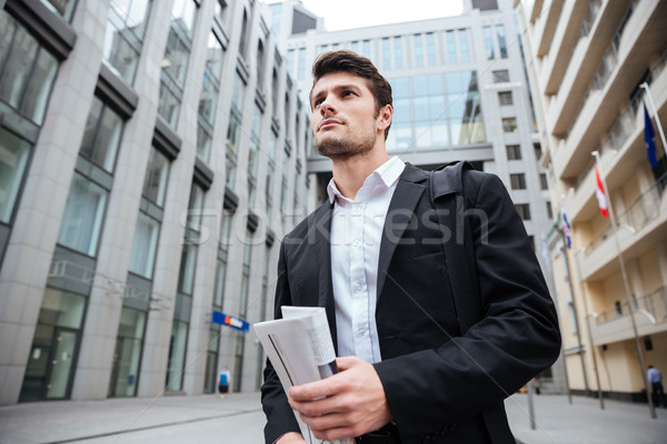 Businessman with newspaper walking in the city Stock photo © deandrobot