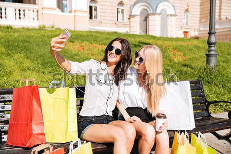 Women resting on the bench and listening music after shopping Stock photo © deandrobot