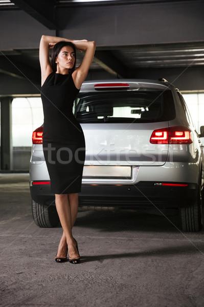 Attractive businesswoman standing near her car on parking Stock photo © deandrobot