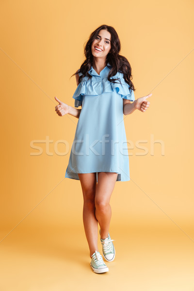 Full length portrait of charming woman showing thumbs up Stock photo © deandrobot