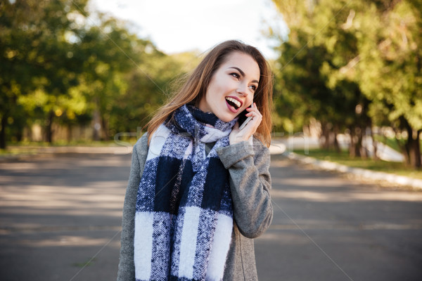 Young happy woman wearing scarf talking on telephone Stock photo © deandrobot