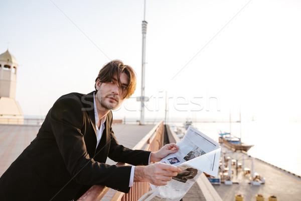 Businessman stood reading the newspaper Stock photo © deandrobot