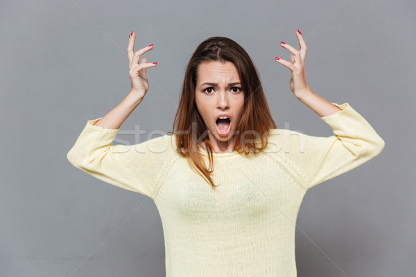 Angry irritated woman with hands raised shouting at camera Stock photo © deandrobot