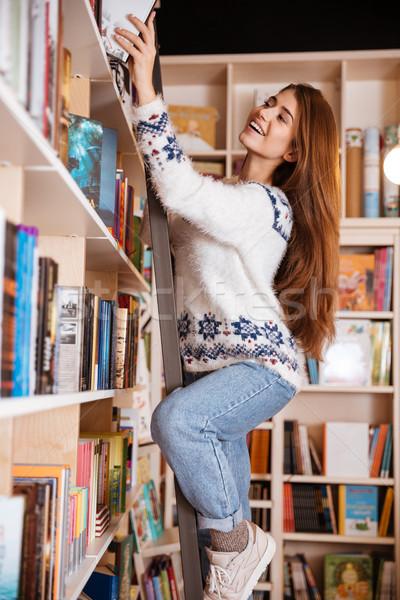 Sorridente estudante livro prateleira biblioteca Foto stock © deandrobot