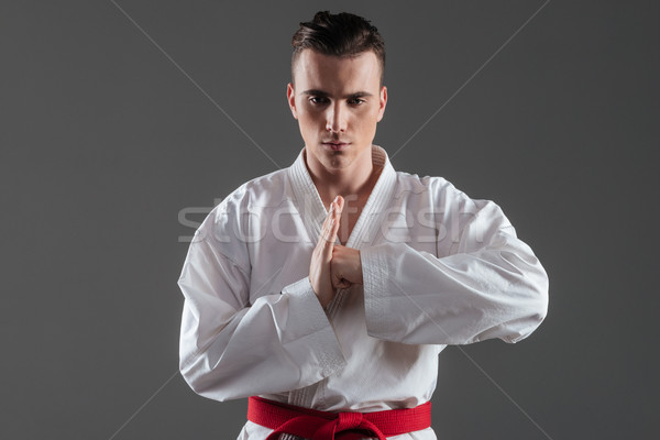 Young sportsman dressed in kimono gesturing with hands Stock photo © deandrobot