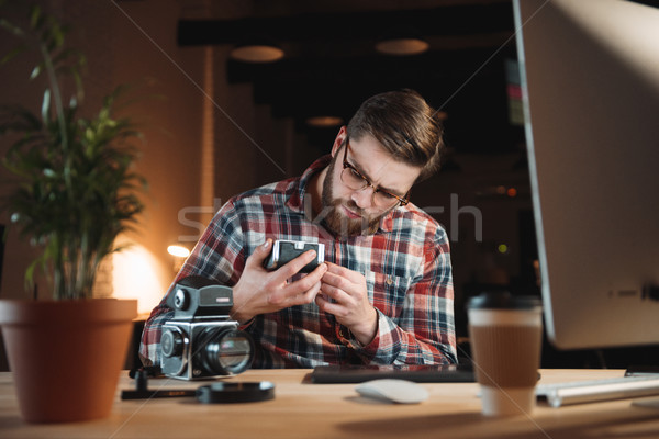 Young bearded man in shirt trying to fix old camera Stock photo © deandrobot