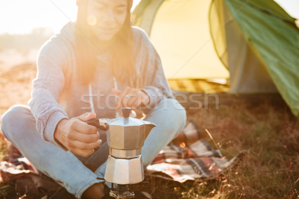 Young traveler woman making coffee outdoors near a tent Stock photo © deandrobot