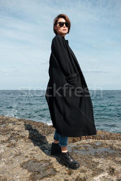 Woman in sunglasses and black coat walking on seashore Stock photo © deandrobot