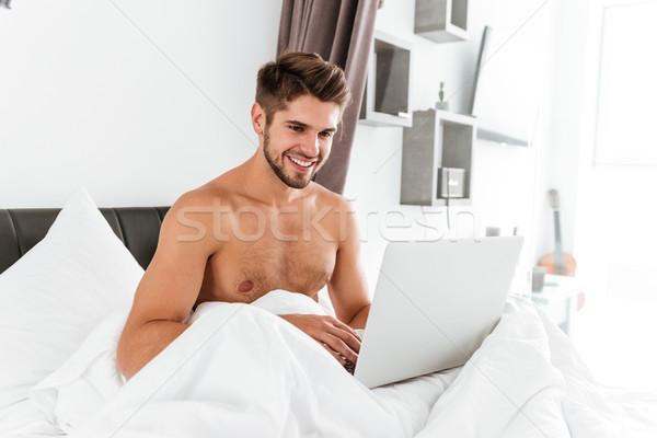 Torse nu jeune homme utilisant un ordinateur portable lit séance Photo stock © deandrobot