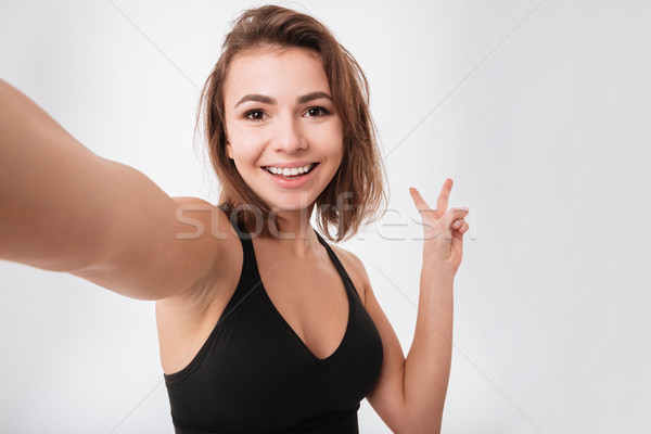 Happy young fitness woman make a selfie with peace gesture Stock photo © deandrobot