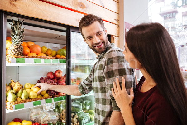 Couple standing and choosing vegetables in grocery shop Stock photo © deandrobot