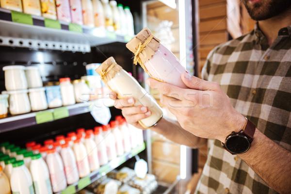 Homme permanent achat yaourt bouteilles épicerie Photo stock © deandrobot