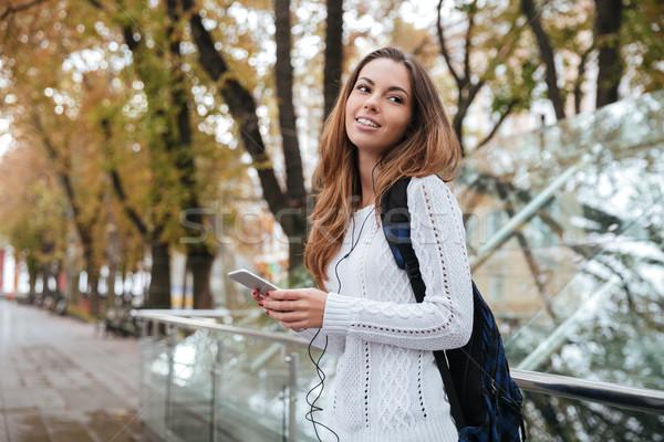 улыбающаяся женщина рюкзак сотового телефона улыбаясь привлекательный Сток-фото © deandrobot