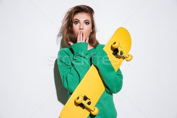 Pretty shocked skater lady with skateboard. Stock photo © deandrobot