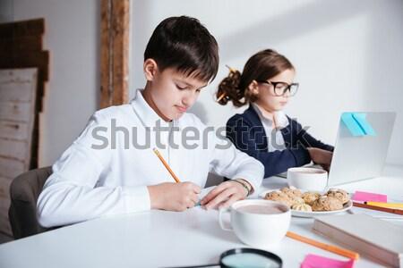 Sério pequeno crianças usando laptop café da manhã menino Foto stock © deandrobot