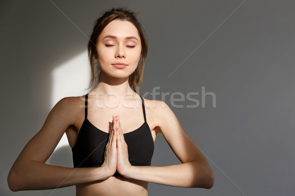Young beautiful woman sitting in asana yoga position Stock photo © deandrobot