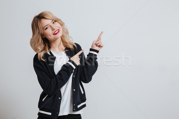 Portrait of a smiling young woman pointing finger away Stock photo © deandrobot