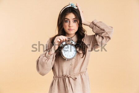 Portrait of a tired young woman holding alarm clock Stock photo © deandrobot