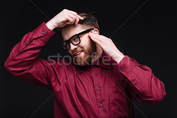 Smiling Male nerd combing his hair Stock photo © deandrobot