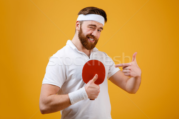 Sportsman holding racket for tennis pointing and showing thumbs up. Stock photo © deandrobot