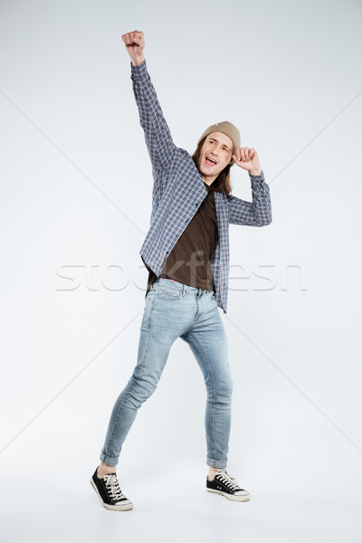 Stock photo: Vertical image of happy hipster posing in studio