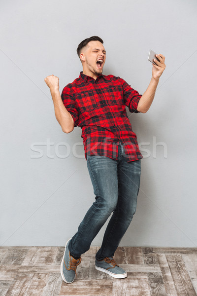 Screaming young man using mobile phone make winner gesture. Stock photo © deandrobot