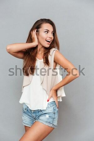 Smiling pretty woman posing sideways Stock photo © deandrobot