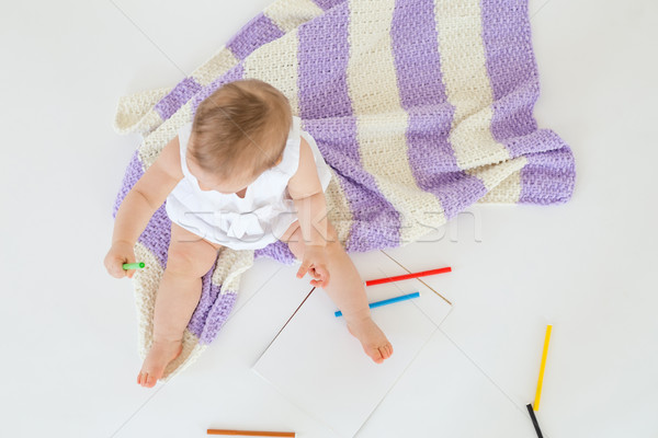 Little baby sitting on floor on plaid near markers Stock photo © deandrobot