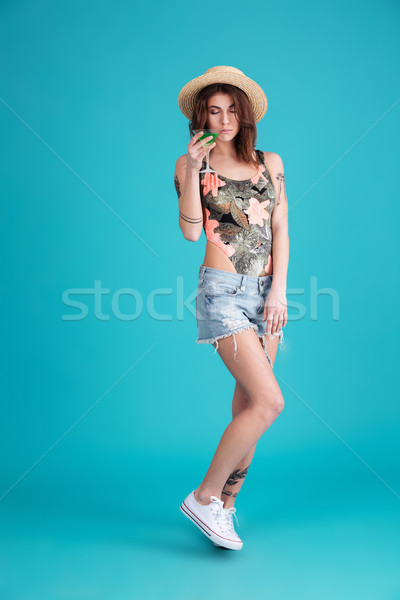Woman holding cocktail isolated over blue background Stock photo © deandrobot