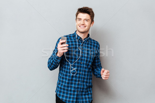 Positive man dancing while listening music on smartphone Stock photo © deandrobot