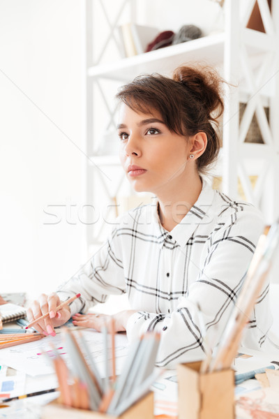 Young attractive female designer creating new clothes Stock photo © deandrobot