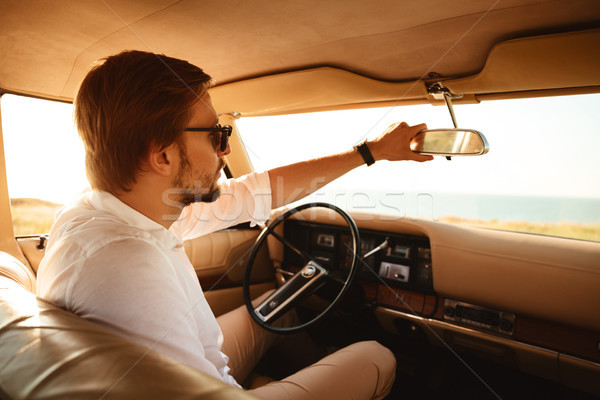 Stock photo: Young handsome man in sunglasses sitting inside his car